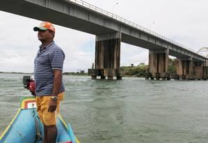 No município de Propriá, o pescador Sebastião Angelo passa por ponte onde a marca d'água no pilar mostra onde chegava o nível do rio Foto: Michel Filho / O Globo