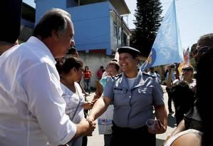 Pezão comprimenta moradores e policial da UPP durante visita ao Batan Foto: Marcos Tristão / Marcos Tristão