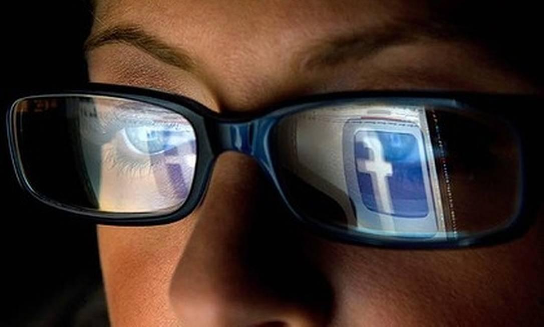 Usuária visualiza sua tela no Facebook Foto: / AFP