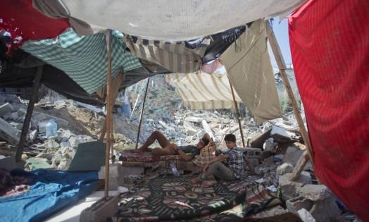 Jovens tentam descansar em barraca improvisada Foto: Khalil Hamra / AP