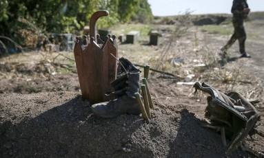 Militar ucraniano passa por cova anônima próximo à Luhansk, no Leste da Ucrânia. Casa Branca diz que soldados russos têm cruzado a fronteira e acredita que Rússia prepara ação militar na região Foto: GLEB GARANICH / REUTERS