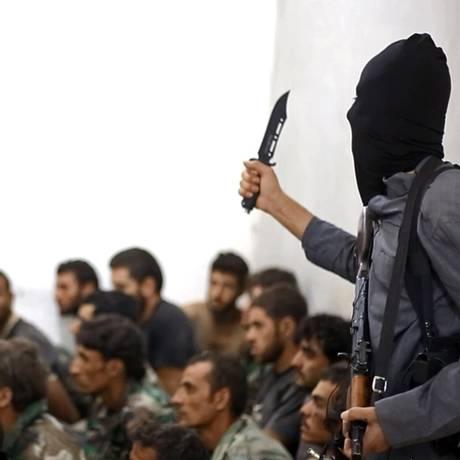 Com uma faca e um rifle, um jihadista do Estado Islâmico ameaça soldados sírios capturados Foto: AP