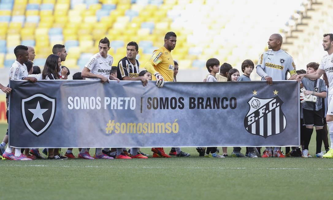 Jogadores de Botafogo e Santos entram em campo com faixa contra o racismo Foto: Alexandre Cassiano / Agência O Globo