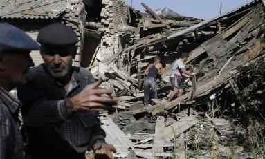 Moradores vasculham as ruínas de um edifício danificado durante os combates na cidade de Ilovaisk, no Leste da Ucrânia Foto: Sergei Grits / AP