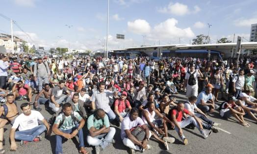Manifestantes sentam no chão e fecham a Avenida das Américas na manhã desta terça-feira Foto: Márcia Foletto / O Globo
