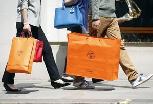 Pedestrem carregam sacola com a marca exclusiva da Hermès em Londres: acordo com a LVMH põe fim à disputa de quatro anos Foto: Simon Dawson / Bloomberg/31-5-2013