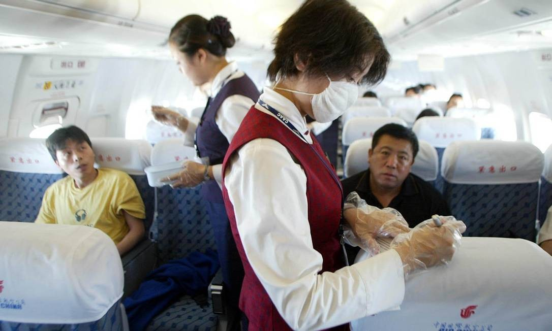 Flight attendants take passenger's temperatures and check health declarations near the end of an Air China flight from Beijing to Chongqing, in central China Thursday June 5, 2003. China's airline industry has been hit hard by the SARS virus outbreak, causing airlines to cancel flights and delay the delivery of new aircraft. China's government has put together a package of financial assistance to help the industry weather the crisis. (AP Photo/Greg Baker) Foto: Greg Baker