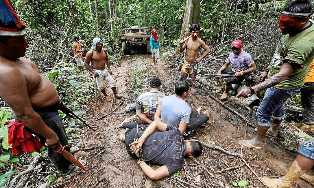 Os guerreiros Ka'apor imobilizam invasores durante a operação realizada em 7 de agosto. Eles seriam supostamente entregues a policiais Foto: Lunaé Parracho/Reuters