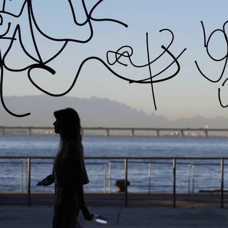 Uma visitante passa pela obra do mexicano Damian Ortega na ArtRio; o artista fotografou pichações de um prédio no Leblon e as reproduziu em ferro Foto: Ana Branco
