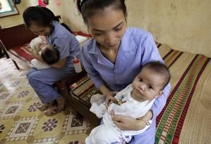 Funcionárias cuidam de bebê em orfanato de Bac Ninh. A foto foi feita em 2008, antes da proibição Foto: Chitose Suzuki / AP