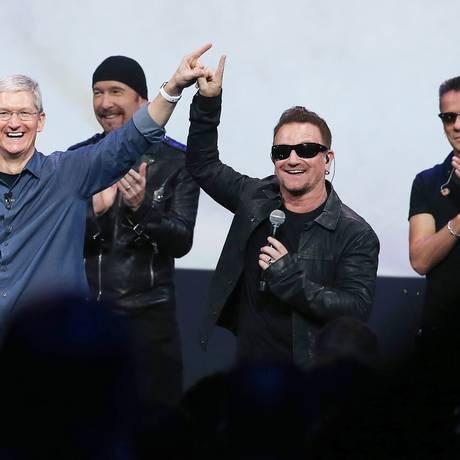 O diretor executivo da Apple, Tim Cook, e o U2: novo álbum irritou usuários do iTunes Foto: JUSTIN SULLIVAN / AFP