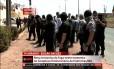 Policiais, do lado de fora da penitenciária, tentam conter a fuga dos presos