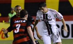 Conca, do Fluminense, domina a bola, marcado por um jogador do Vitória, no Barradão Foto: Mauro Akin Nassor / Photocamera
