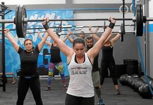 Participação feminina. Mulheres formam boa parte do grupo de praticantes de CrossFit: em primeiro plano, Camila Maciel levanta 45 quilos Foto: Pedro Teixeira / Pedro Teixeira