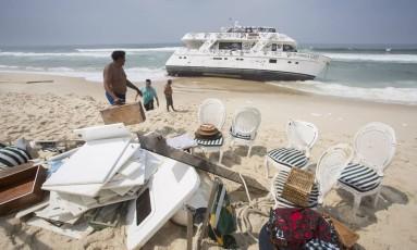 Homens retiram objetos para desmontagem da embarcação Foto: Daniela Dacorso / Agência O Globo