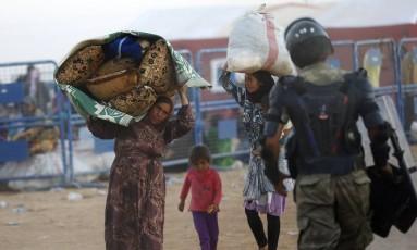 Mulheres curdas da Síria carregam pertences depois de passarem para a Turquia, perto da cidade de Suruc Foto: MURAD SEZER / REUTERS