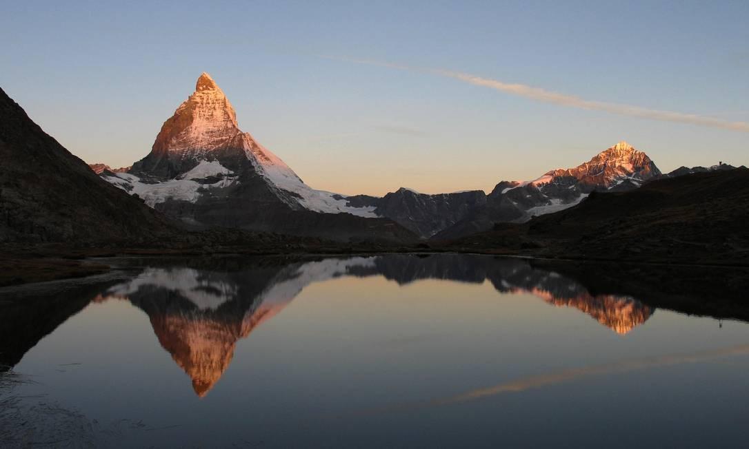 A montanha Matterhorn ao amanhecer, vista a partir do lago Riffelsee, perto de Zermatt, na Suíça Foto: Kurt Müller / Turismo de Zermatt/Divulgação