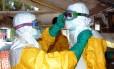 Profissionais de saúde vestem traje protetor contra o ebola ao entrarem no centro de tratamento de infectados com o ebola, em Conacri, na Guiné
