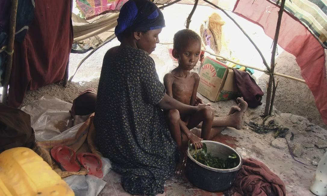 Criança desnutrida no Sul da Somália, no colo da mãe. O país, considerado um Estado falido, continua a ter o pior índice da Africa em desenvolvimento humano Foto: AP-25-07-2011