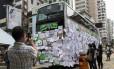 Em Hong Kong, homem fotografa com seu celular um ônibus coberto de mensagens de apoio aos protestos