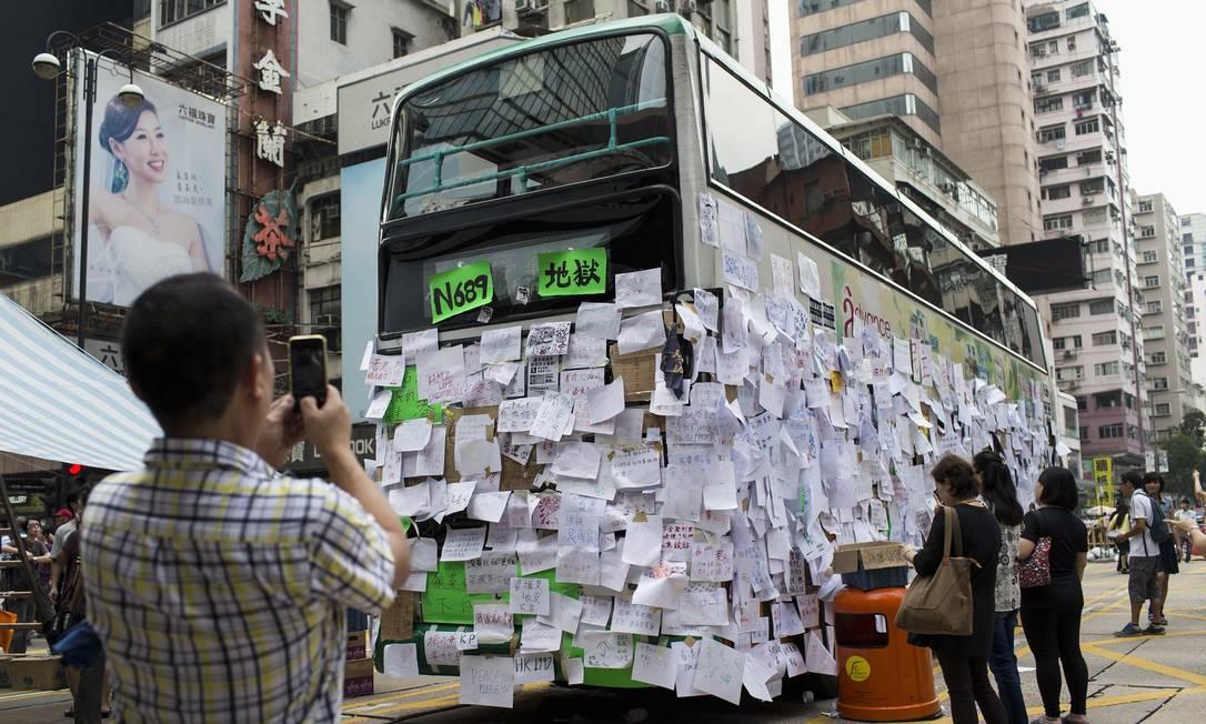 Em Hong Kong, homem fotografa com seu celular um ônibus coberto de mensagens de apoio aos protestos Foto: TYRONE SIU / REUTERS