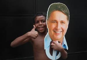 Garoto segura máscara de Garotinho em visita do candidato pelo Complexo de Favelas da Penha, na Zona Norte do Rio Foto: Kátia Carvalho / Parceira / Agência O Globo Foto: Terceiro / Agência O Globo