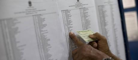 Homem procura seu nome em lista de seção eleitoral na Rocinha em outubro de 2014 Foto: Silvia Izquierdo / AP