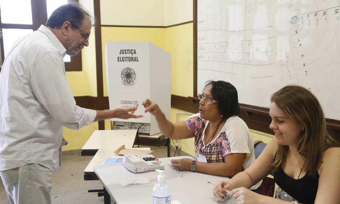 Eleitor diante dos mesários em seção de Niterói Foto: Ana Branco / Agência O Globo