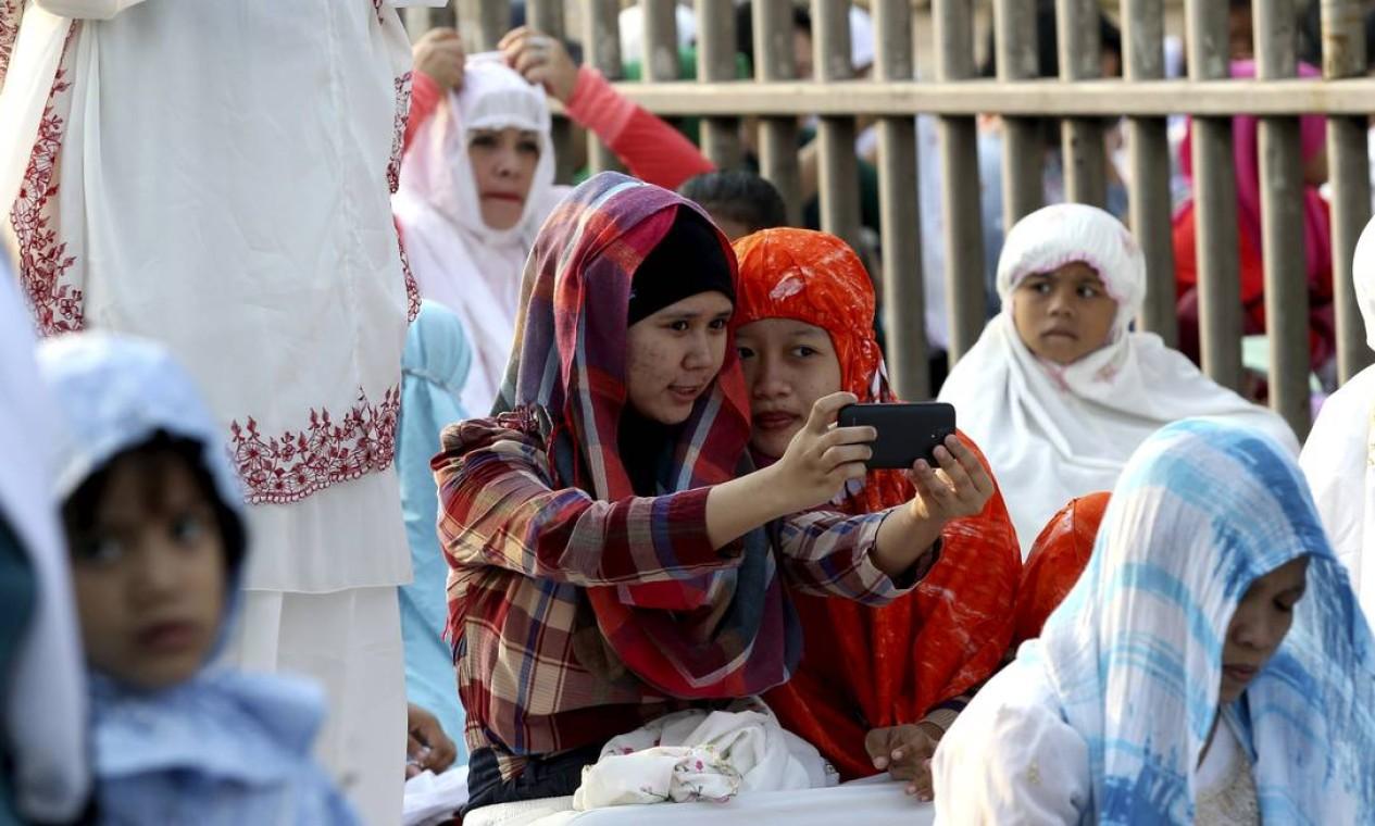 Muçulmanas tiram 'selfie' antes de uma oração pela manhã em uma rua de Jacarta, na Indonésia Foto: Tatan Syuflana / AP