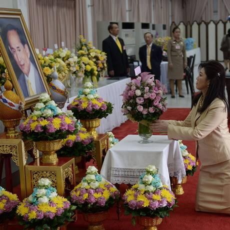 Ex-primeira-ministra da Tailândia, Yingluck Shinawatra reza em frente ao retrato do rei Bhumibol Adulyadej Foto: AFP/Christophe Archambault