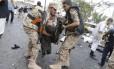Rebeldes Houthi carregam o corpo de um homem morto no atentado suicida no centro de Sanaa