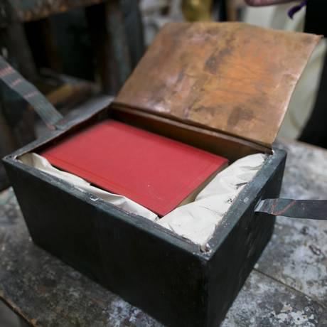 Um livro de capa dura vermelha foi encontrado dentro da cápsula do tempo escondida no museu Old State House, em Boston Foto: DOMINICK REUTER / REUTERS