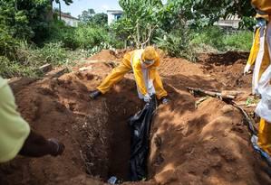 Agentes de saúde enterram corpo de vítima de ebola em Freetown, em Serra Leoa Foto: FLORIAN PLAUCHEUR / AFP