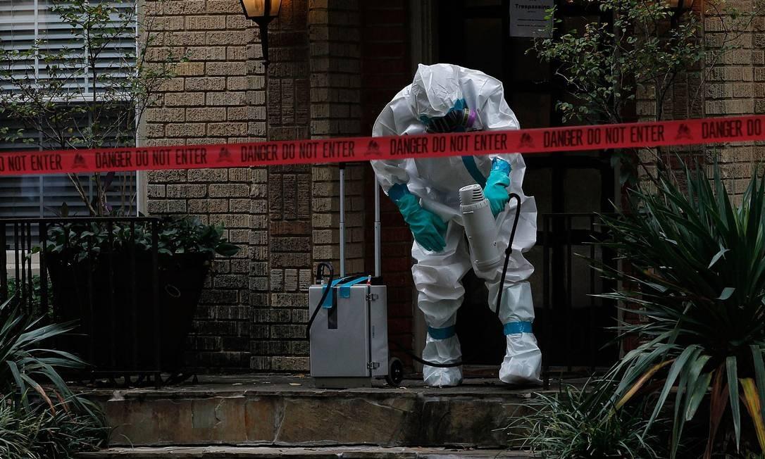 Homem com roupas de proteção isola área em volta da casa da enfermeira americana infectada por ebola no Texas Foto: MIKE STONE / AFP