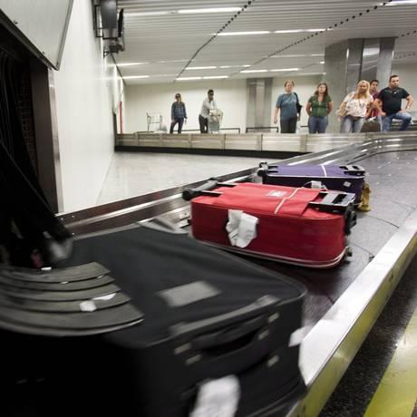 Passageiros aguardam suas malas no Galeão Foto: Guito Moreto / Agência O Globo