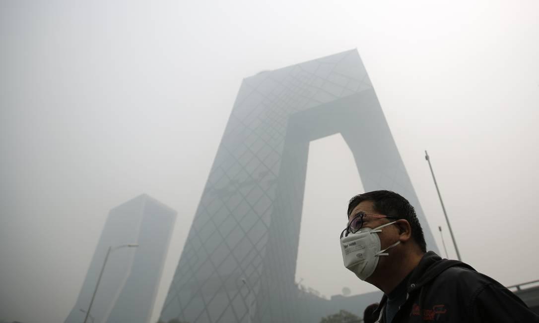 """Homem usa máscara para se proteger da poluição em frente a edifício que quase """"desaparece"""" na névoa Foto: KIM KYUNG-HOON / REUTERS"""