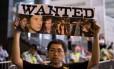 Homem segura um cartaz com as fotos dos policiais suspeitos de bater em um manifestante em Hong Kong