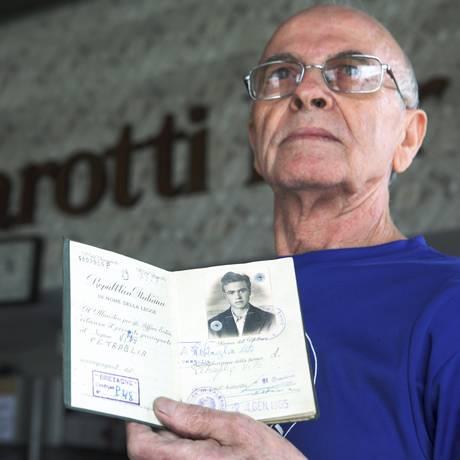 Em seu bar na Ponta D'Areia, o italiano Vito Petraglia mostra o passaporte com o qual entrou no Brasil, em 1955 Foto: Gustavo Stephan / Agência O Globo