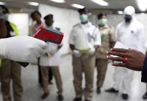 Autoridades usam termômetros para monitorar passageiros no Aeroporto Internacional de Lagos, na Nigéria Foto: Sunday Alamba / AP
