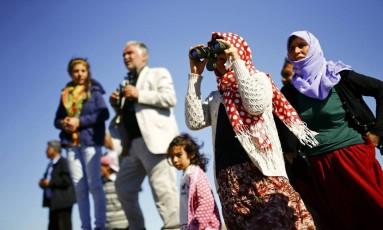 Curdos turcos olham a cidade síria de Kobani de uma colina perto de Mursitpinar, na fronteira turco-síria na cidade do sudeste de Suruc, na província de Sanliurfa Foto: KAI PFAFFENBACH / REUTERS