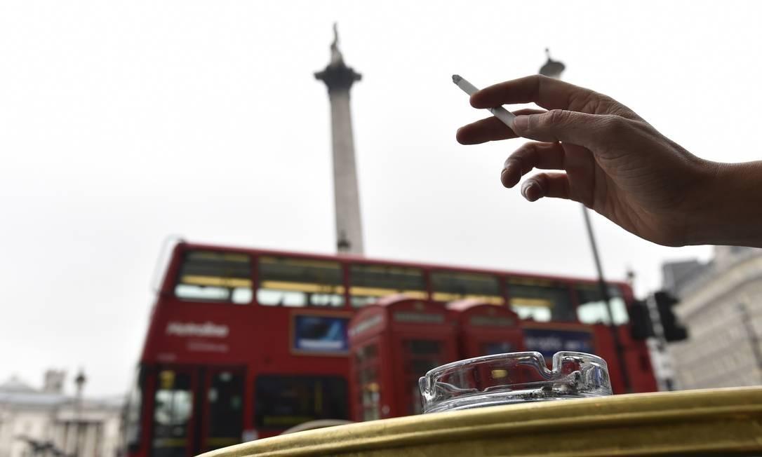 Uma mulher fuma na Trafalgar Square, em Londres: projeto de lei quer banir o cigarro dos espaços públicos da cidade: ações restritivas ganham novo ímpeto Foto: TOBY MELVILLE / REUTERS