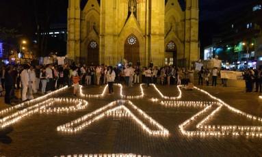 """Colombianos escrevem """"Paz"""" usando velas em junho, após anúncio de diálogos entre o governo e o ELN. Grupo agora afirma que manterá diálogos separados das negociações travadas pelas FARC Foto: DIANA SANCHEZ / AFP"""
