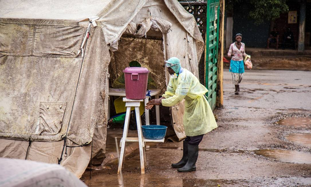 Funcionário de saúde lava as mãos antes de entrar em uma tenda de teste para o ebola Foto: Michael Duff / AP