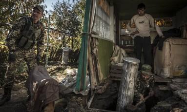 Separatistas retiram parte de um projétil BM-27 Uragan, que teria carregado bombas de fragmentação, em Ilovaisk, Ucrânia: Human Rights Watch denunciou 12 ataques Foto: SERGEY PONOMAREV / NYT