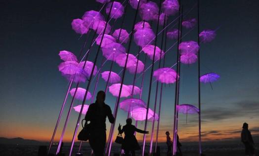 Pessoas passam pela instalação ''Umbrellas' iluminada de rosa, como parte da campanha de prevenção ao câncer de mama Foto: SAKIS MITROLIDIS / AFP