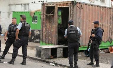 Policiais em frente ao contêiner da UPP no Lins de Vasconcenlos, que foi incendiado durante um protesto de moradores Foto: Fabiano Rocha / Agência O Globo