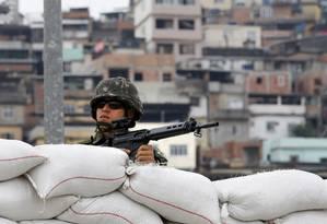 Militares patrulham a Vila dos Pinheiros, uma das favelas do Complexo da Maré Foto: Ivo Gonzalez / Agência O Globo