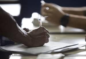 Eleitor assina ata de votação em escola de Copacabana, no Rio Foto: Márcia Foletto / O Globo