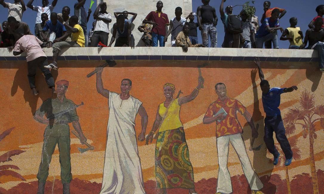 Manifestantes sobem em muro em frente à Praça da Nação, em Ouagadougou, capital de Burkina Faso Foto: JOE PENNEY / REUTERS