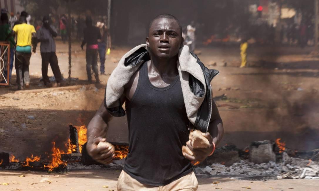 Ativistas reagiram atirando pedras contra os policiais Foto: JOE PENNEY / REUTERS
